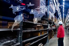 Male manager using handheld in a large warehouse worker checking delivering boxes. distribution center. Logistics concept stock photography