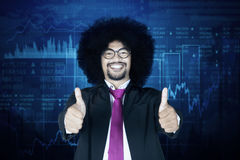 Male manager with virtual financial statistic. Image of Afro male manager showing thumbs up at the camera while standing with a virtual financial statistic Stock Image