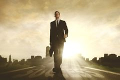 Male manager walking above success word. Low angle view of young male manager walking above success word on the road while holding a briefcase Royalty Free Stock Photography