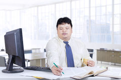 Male manager writes on paper in office Stock Image