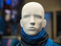 Male mannequin with a blue and black scarf around his neck. Male mannequin in the background of a sports store under artificial lighting Royalty Free Stock Images