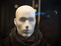 Male mannequin on a dark background of a shop window. Head of a mannequin with a scarf around his neck behind the shop window under artificial lighting Stock Images