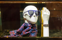 Male mannequin head in sunglasses and scarf. Male mannequin head in modern sunglasses and stylish scarf, dummy hand in leather bracelet. Vintage clothes in Stock Image