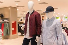 Male mannequins in jacket, shirt and baseball cap. Male mannequins in red jacket, gray shirt and black baseball cap. Fashion store interior on background Stock Photography