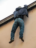 Male mannnequin hanging from the edge of a building Royalty Free Stock Image