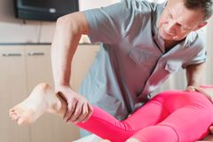 Male manual visceral therapist masseur treats a young female patient. Work with the buttocks of the lower back and royalty free stock images