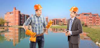 Manual worker having a conversation with architect, buildings in Stock Image