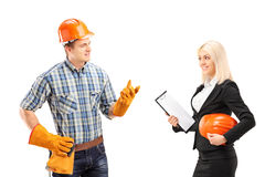Male manual worker having a conversation with female architect. Isolated on white background Stock Photos