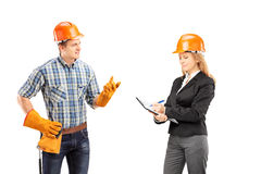 Male manual worker having a conversation with female architect. Isolated on white  background Royalty Free Stock Image