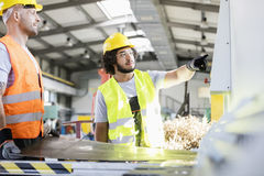 Male manual workers manufacturing sheet metal at factory stock photography