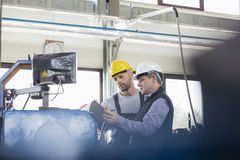 Male manual workers operating machinery at metal industry stock image