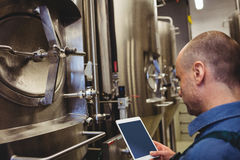 Male manufacturer using digital tablet by machinery Royalty Free Stock Image