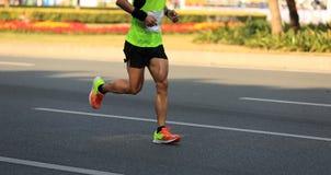 Male marathon runner running on city road. Fitness male marathon runner running on city road Stock Photos