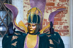Male mask in S.Marco's Square. Male mask in creative costume at Carnival in Venice in turqoise, gold and violet Royalty Free Stock Photography