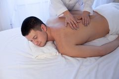 Male masseur doing massage back spa health. Male massage therapist does the procedure Massage Spa health Stock Photo