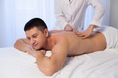 Male masseur doing massage back spa health. Male massage therapist does the procedure Massage Spa health Stock Image