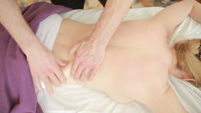 Male massage therapist doing back massage to woman. Massage specialist massaging woman s back at beauty salon. Male massage therapist doing back massage to woman stock footage