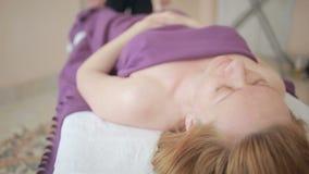 Male massage therapist doing foot massage for women. Massage specialist massaging woman s back at beauty salon. Male massage therapist doing foot massage for stock footage
