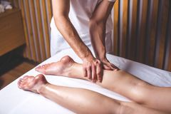 A male massage therapist massages the female legs in the massage parlor. Hands of the masseur make a foot massage lying on the couch. Legs lie on a white couch Royalty Free Stock Image