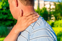 Male massaging sore shoulder. Outdoors Stock Image