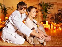 Male masseur doing massage woman in bamboo spa. Stock Photo
