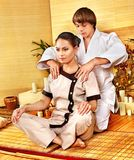 Male masseur doing massage woman in bamboo spa. Male masseur doing massage young woman in bamboo spa Royalty Free Stock Photography