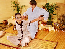 Male masseur doing massage woman in bamboo spa. Royalty Free Stock Photography