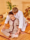 Male masseur doing massage woman in bamboo spa. Male masseur doing massage young women in bamboo spa. Sitting girl Stock Image