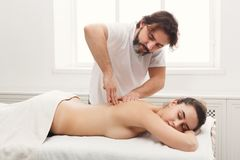 Male masseur doing professional body massage. Male masseur massaging female back and shoulders. Professional body treatment or relaxation procedure at spa salon Royalty Free Stock Images