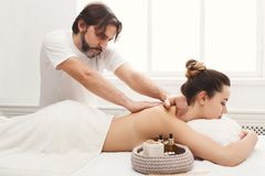 Male masseur doing professional body massage. Male masseur massaging female back and shoulders. Professional body treatment or relaxation procedure at spa salon Stock Photo