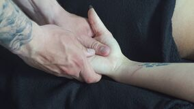 Male masseur makes palm massage hands for a young girl.