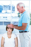 Male masseur massaging head of pregnant woman. Male masseur masaging head of pregnant women at health center Royalty Free Stock Image