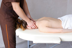 Male masseur with strong hands kneads neck of young woman who li Royalty Free Stock Images