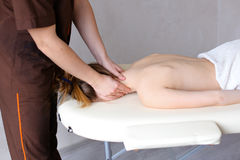 Male masseur with strong hands kneads neck of young woman who li Stock Photos