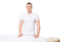 Male masseur is waiting for a patient near a massage table. In isolation Royalty Free Stock Images