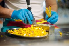Master hands in gloves, caramel making process. Male master hands in gloves, caramel making process. Candy preparation in pastry shop Royalty Free Stock Images