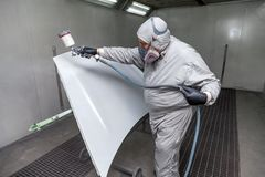 A male master worker paints with a spray gun a part of the car body in silver after being damaged at an accident. Hood from the royalty free stock photos