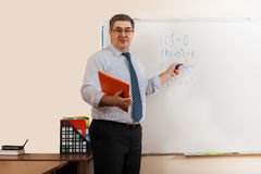 A male mathematics teacher shows on the blackboard Royalty Free Stock Photo
