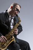 Male Mature Saxophone Player in Sunglasses Playing the Saxophone. While Sitting on Chair in Studio Environment. Vertical Image Royalty Free Stock Photo