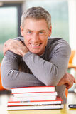 Male Mature Student Studying In Classroom With Books. And Smiling Royalty Free Stock Photos