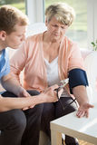 Male measures the pulse of an older woman Royalty Free Stock Photos