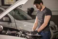 Mechachic checking on car engine and taking notes in clipboard. Male Mechachic checking on car engine and taking notes in clipboard Stock Photography