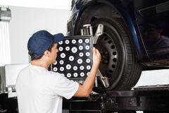 Male Mechanic Adjusting Wheel Alignment Machine. On car tire in garage Royalty Free Stock Images