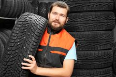 Male mechanic with car tire. In automobile store Stock Photos