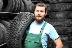 Male mechanic with car tire. In automobile store Stock Photo