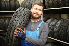 Male mechanic with car tire. In automobile store Royalty Free Stock Photography