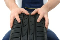 Male mechanic with car tire. On white background, closeup Stock Photo