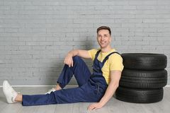 Male mechanic with car tires. On brick wall background Royalty Free Stock Image