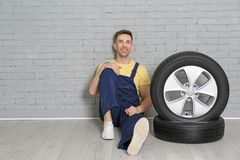 Male mechanic with car tires. On brick wall background Stock Images
