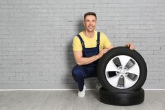 Male mechanic with car tires. On brick wall background Royalty Free Stock Photo